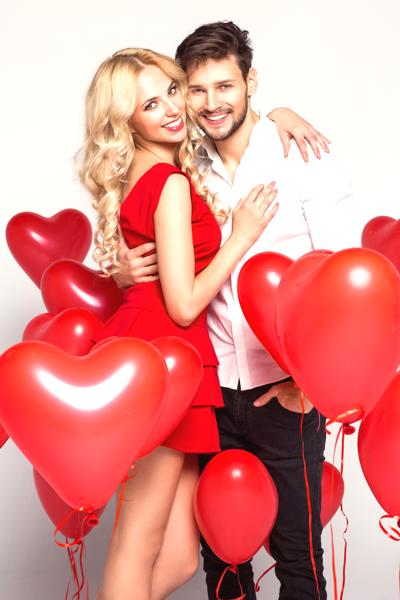 Glückliches Hochzeitspaar mit Herzluftballons