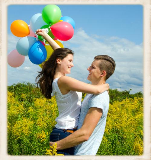 junges Paar mit heliumgefüllten Luftballons